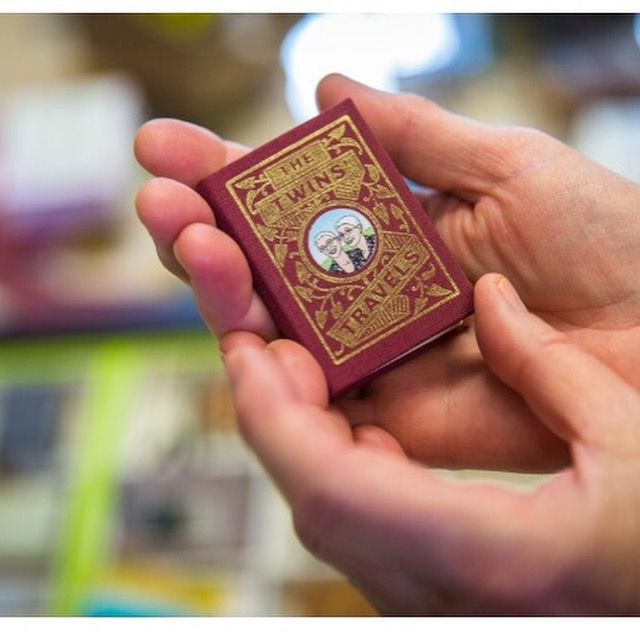 A tiny red book in a person's hands