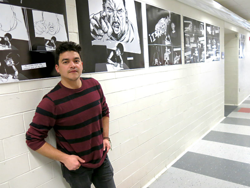 German Andino standing next to his #NoHumanIsAlien exhibition at U-M