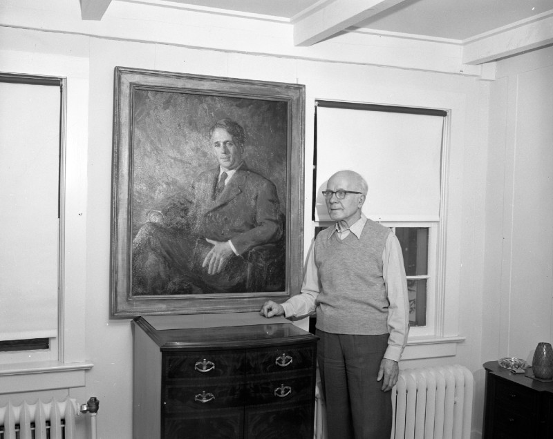 Leon Makielski standing by his portrait of Robert Frost; photo by Eck Stanger in the Ann Arbor News